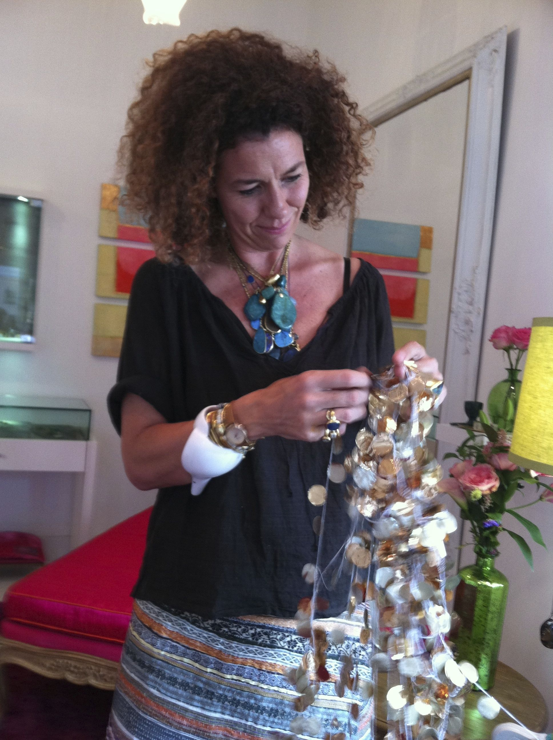 Wearing jewels she designed, a Paul Smith watch and a groovy giant shell bracelet given to her by African artisans, Pippa Small prepares gilded window display materials during a summer 2014 visit to her Brentwood Country Mart boutique. Photo by Kyle Roderick.