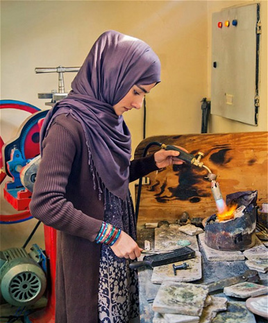 One of Turquoise Mountain's jewelers at work in the Kabul atelier. Since 2006, the charity has trained hundreds of women and men in jewelry making and stone cutting. Photo courtesy Pippa Small.